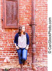 meisje, leun, rode baksteen muur