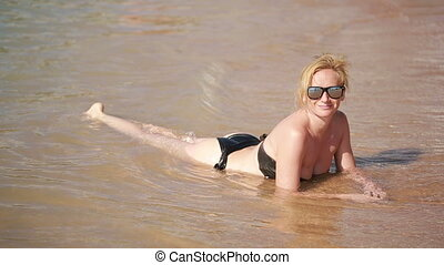 meisje, liggend op het strand, in, water., zomer, rusten