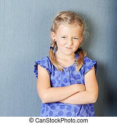meisje, met, gekruiste wapens, gezichten het trekken, tegen, blauwe muur