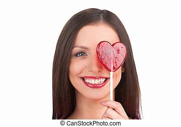 meisje, met, lollipop., verticaal, van, mooi, jonge vrouw , vasthouden, hart gedaante, lollipop, voor, haar, oog, terwijl, vrijstaand, op wit