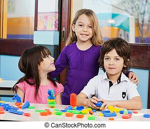 meisje, met, vrienden, spelend, blokjes, in, klaslokaal