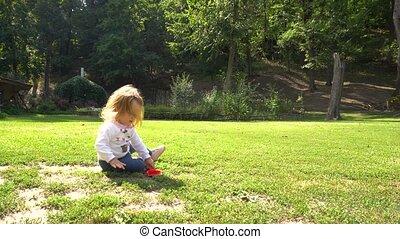 meisje, speelgoed, gras, spelend, zittende