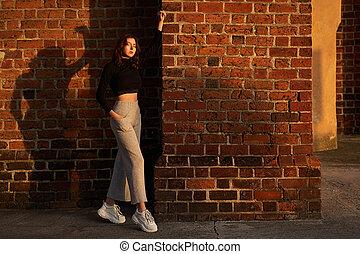 meisje, verticaal, het poseren, baksteen, licht, lang, hoog, broek, mooi, mouw, muur, vervelend, jersey, achtergrond, sensueel, black , zonlicht, breed, t-shirt, taille, gieten, grijze , roodharige, schaduw, rode zonsondergang, been