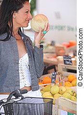 melão, mulher, mercado, cheirando