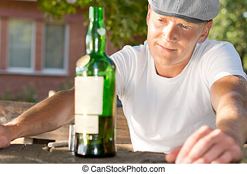 Horizontal portrait of a melancholic drunk man looking at a bottle of alcoholic beverage