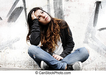 A young woman listening to melancholic Music and sitting on the pavement.