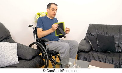 Melancholic sad young disabled man looking at a photo