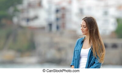 Melancholic woman looking away outdoors in a coast town