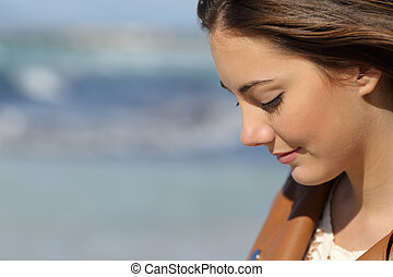 Close up portrait of a melancholic woman thinking on the beach with the sea in the background