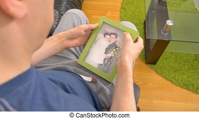 Melancholic young disabled man looking at a photo -...