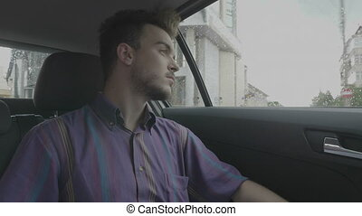 Melancholic young man dreaming and looking through the car...