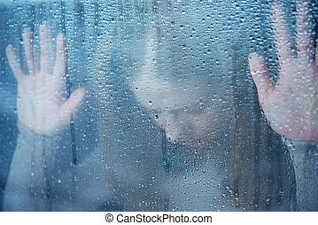 hand of young woman melancholy and sad at the window in the rain