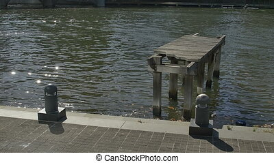 Old wooden dock on Yarra river at one time used as a crossing bridge in Southbank Melbourne.
