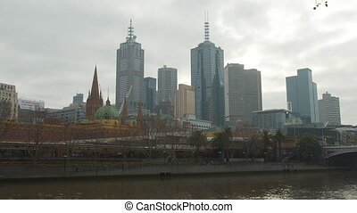 Wide low angle daytime still shot of Melbourne skyline against grey cloudy sky, Australia