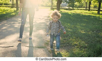 Melenko boy walking along a path in a park. Nice young girl watching him Taken with a Sony camera, slow motion