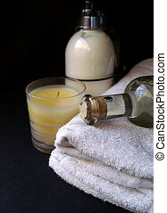 relaxing and mellow cream and scented candle and massage oil with towel to show a relaxing spa treatment