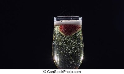 Mellow strawberry in glass with champagne sparkling wine. Slow motion