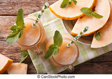 Melon juice in the glass on the wooden table. horizontal top view