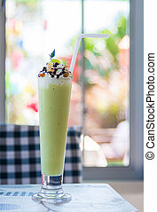 Melon smoothie in glass on a table.