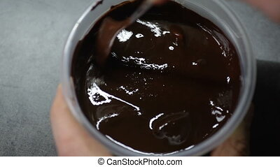 melted chocolate in the jar is stirred with a spoon
