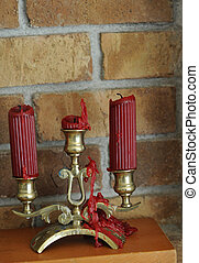 Melted wax candle with red wax dripping down an old golden...