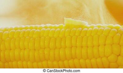 Melting butter on hot freshly boiled corn close-up shot -...