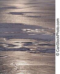 Melting ice tip of the iceberg. The sun shines through cracks