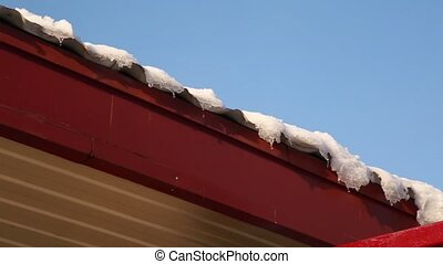 Melting Icicles dripping off a roof. Spring drops, icicles are melting sun and snow.