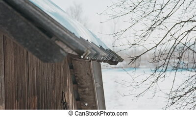 Melting snow on the roof on a sunny spring day, drops of water falling from the roof edge