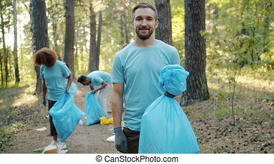 Member of volunteering team holding bin bag with trash in forest smiling at camera