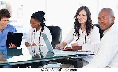Members of a medical tean looking at the camera while...