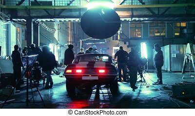 Members of film crew are engaged in installation of equipment round car on set in street