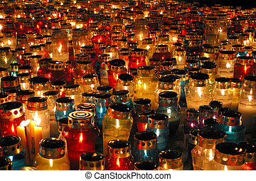 Memorial candles shining at the cemetery on the All Saints...