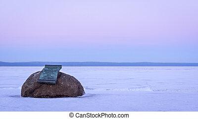 Memorial plaque on boulder on lake