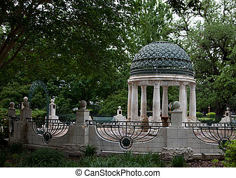 A memorial rotunda with marble columns and a green painted metal dome roof, surrounded by a low wall with railings and trees.6