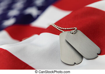 Memorial - Blank dog tags on American flag with focus on...