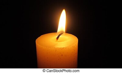 Memorial thick candle with shimmering light the flame against dark black background