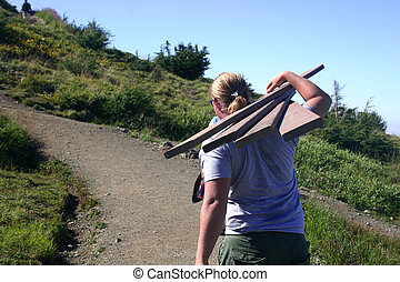 Memorial Trek - Young man carrying lumber up steep mountain...
