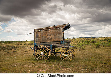 An old west sheriff's wagon sits on the lonesome frontier prarie as storm clouds gather in the distance.