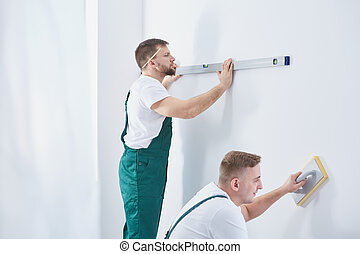 Men and home renovation - Two professional men working...