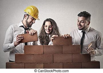 Men and woman builing wall