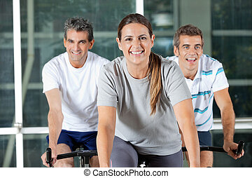 Men And Woman On Exercise Bikes - Happy men and woman on...