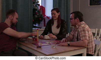 Men and woman play a board game in a cafe
