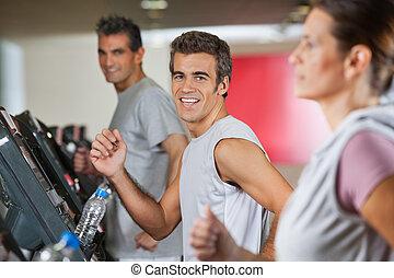 Men And Woman Running On Treadmill