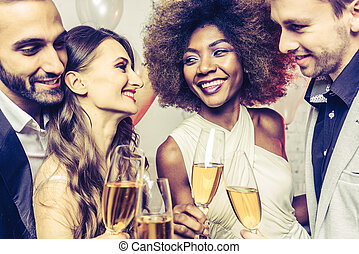 Men and women celebrating while clinking glasses with sparkling wine