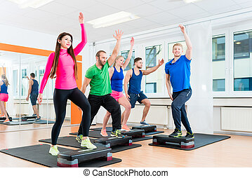 Men and women doing step-aerobics at gym