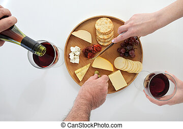 Men and women drinking red wine and eating from a cheese platter