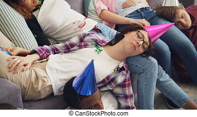 Men and women in party hat sleeping on couch and floor after...