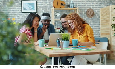 Men and women multi-racial team are using laptop in office talking laughing working at project together. Workplace, emotions and modern technology concept.