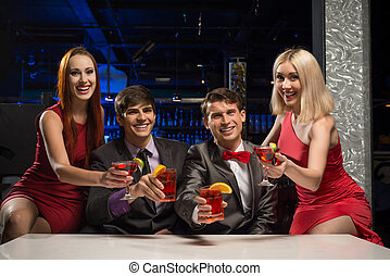Men and women raised their glasses with cocktails